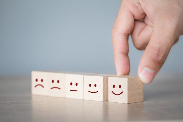 木製キューブ、サービスの評価、満足度の概念にスマイリーの顔の絵文字を押す顧客。
