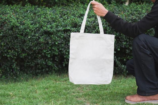 モックアップ、エコロジーコンセプトのバッグキャンバス生地を抱きかかえた。