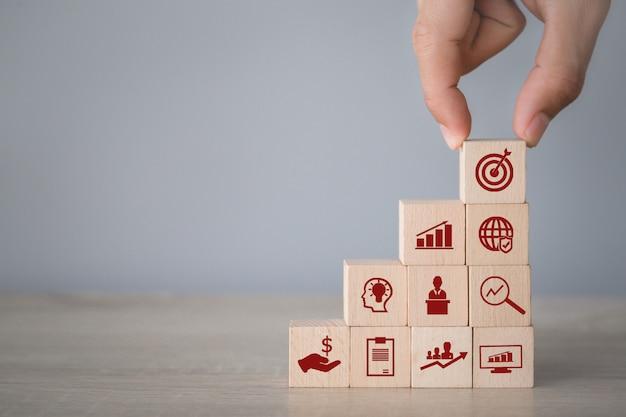 ビジネスコンセプトをターゲットに、アイコンの矢印とビジネスでスタッキングウッドブロックを配置する手。