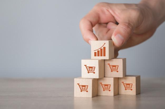 アイコングラフとショッピングカートシンボル上方向にスタッキング木製ブロックを配置する手、