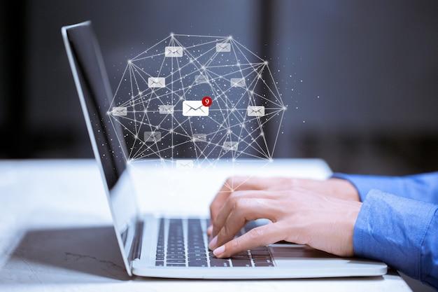 Бизнес используя компьтер-книжку, с значком электронной почты, концепцией графиков электронной связи входящей электронной почты.