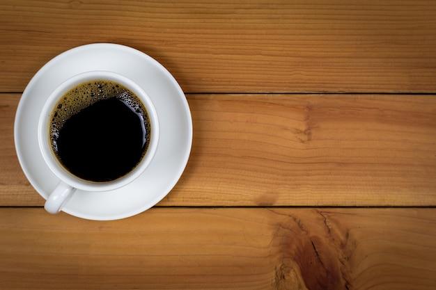 木製の背景、トップビューでコーヒーカップ。