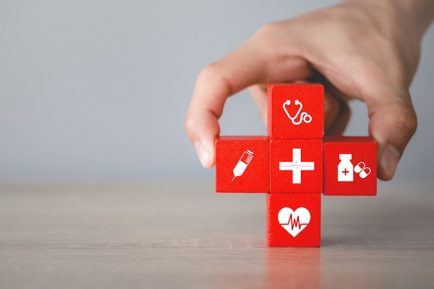 健康保険の概念、アイコン医療医療とスタッキングウッドブロックを配置する手。