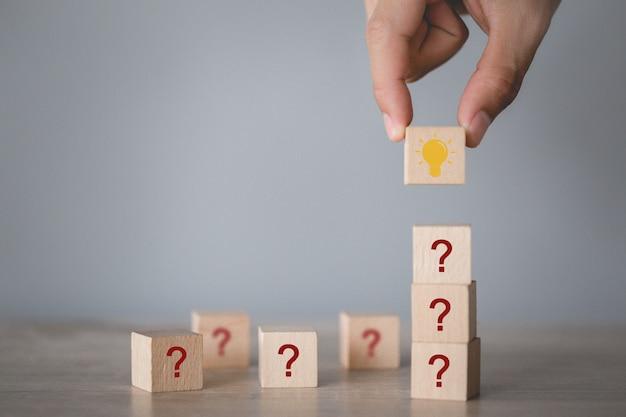Вручите аранжировать деревянный блок штабелируя с вопросительным знаком значка и лампой, думая с концепцией вопросительного знака.