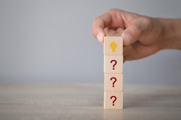 疑問符の概念を考えてアイコン疑問符とランプをスタッキングウッドブロックを配置する手。