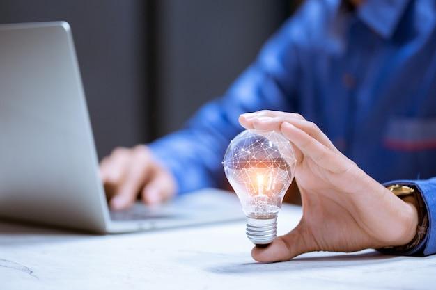 脳のアイコン、創造性と革新性を持つ電球を持っているビジネス手は、成功、新しいアイデア、革新コンセプトの鍵です。