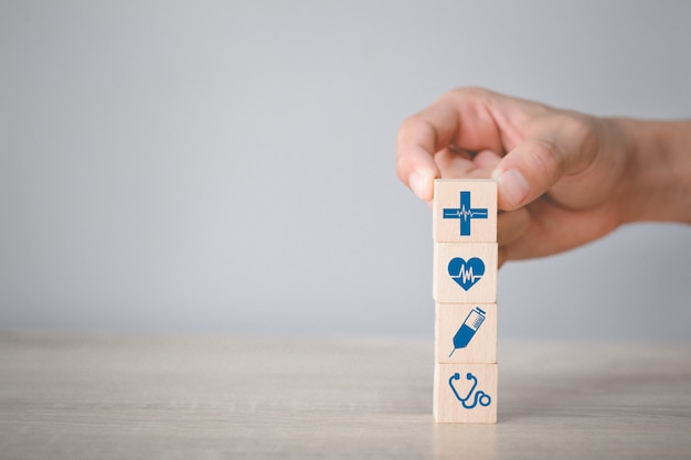 ヘルスケアおよび医療アイコンと積み重ねるウッドブロックを配置する手