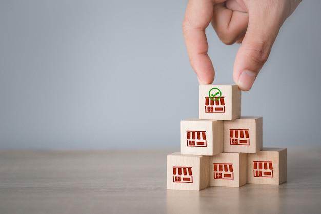 Бизнес-концепция франшизы, рука выбрать деревянный блог с маркетингом франшизы.