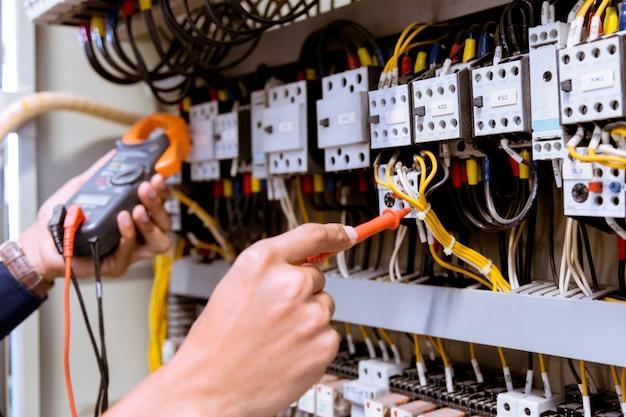 コントロールパネルの電流をマルチメータでテストする電気技師の測定。
