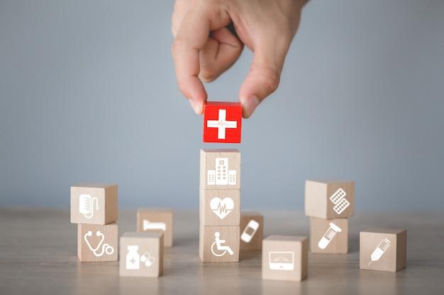 Концепция медицинского страхования, рука, укладка деревянный блок укладки с иконой здравоохранения медицинской.