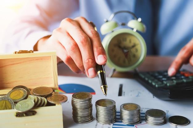 手はお金を節約し、成長しているビジネスコンセプトにお金のコインスタックを置く。
