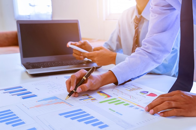 Бизнесмен документы на офисный стол со смартфоном и ноутбуком и двумя коллегами