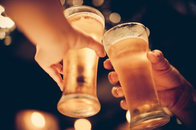 冷たいビールのグラスは美しいボケ味でボトムアップし、友達同士でビールを飲みながら、ダークトーン