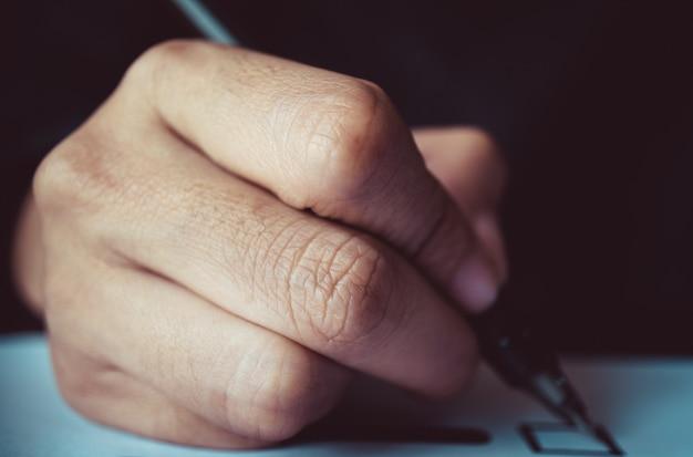 Мужчина держит ручку для отметки на бумаге для голосования