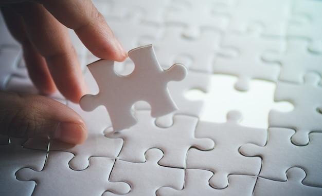 手で保持している白い平らなジグソーパズルの最後の部分、成功の概念のステップ