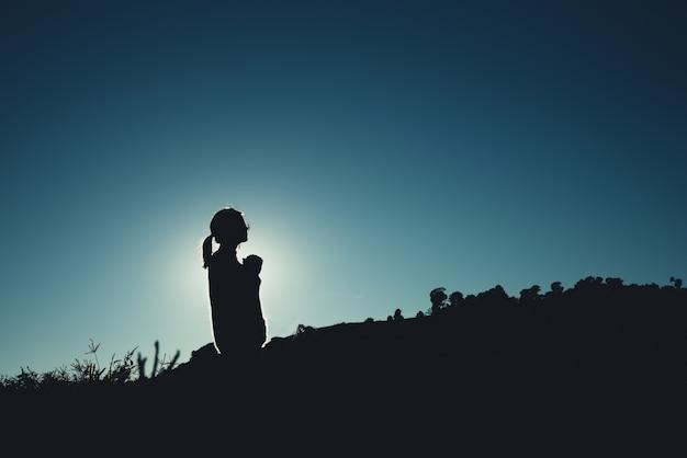 Силуэт азиатской женщины молится на горе
