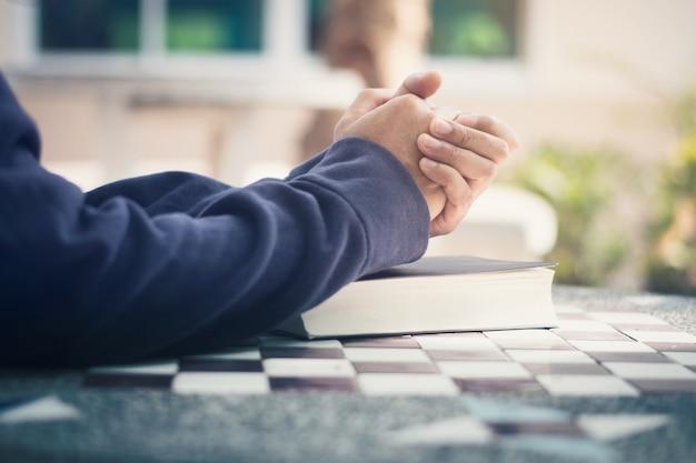 Мужчина держит библию в руках и молится