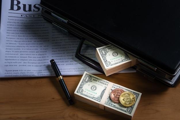 Банкнота в портфеле, ручка, наденьте деловую газету и биткойны на банкноту.