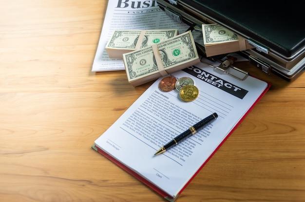 Банкнота в портфеле. положите на бизнес-газету и биткойны, ручку надел контракт