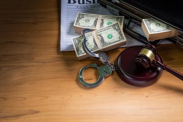 ブリーフケースの手錠のドルビジネスの新聞と木製のハンマーを試着のために置いてください。