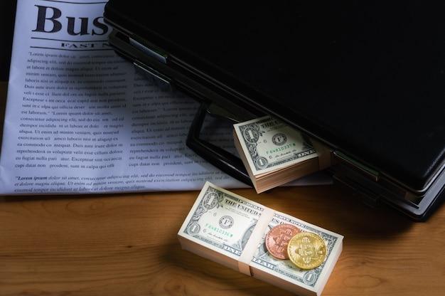 Банкнота в портфеле. положите на деловую газету и биткойны на банкноту.