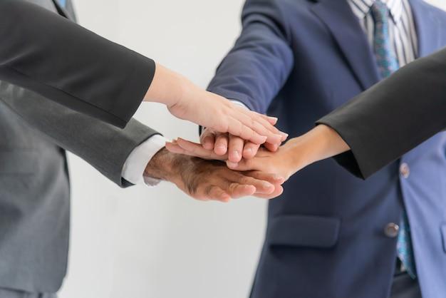 Деловые люди, встречающиеся в команде, взялись за руки, чтобы добиться синергетического успеха.