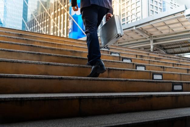 Бизнесмен с портфелем ходить вверх по лестнице
