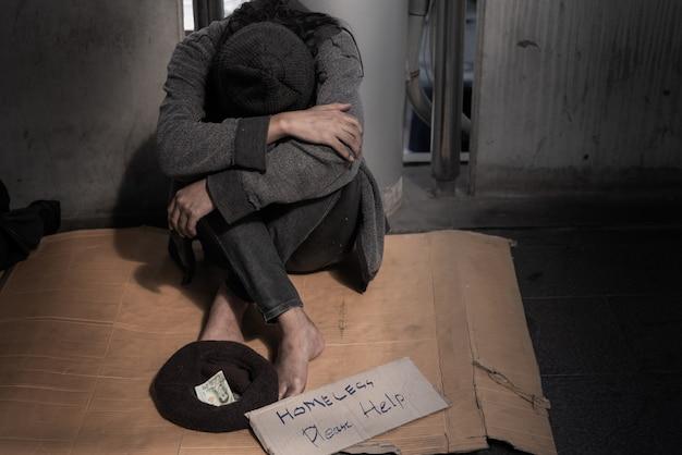 物乞い、ホームレス、床の上に座って、人々からお金のほんの一部を求める。