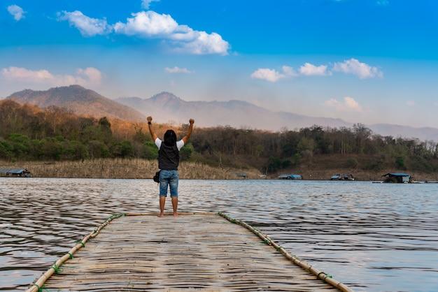 風景画像、男性観光客の裏竹の橋の上に立っています。