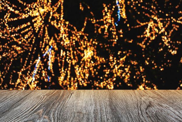 テクスチャ表面の木とゴールドの光ボケ背景。
