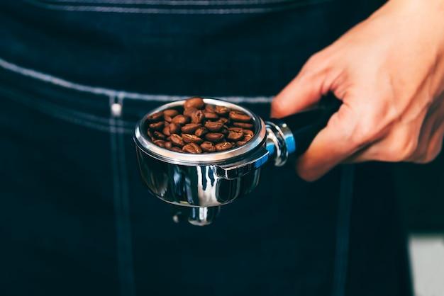 コーヒーメーカーは、コーヒー豆を含むデバイスを持ち、顧客のためにコーヒーを準備します。