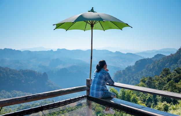 アジアの男性の観光客が太陽を遮る大きな傘を持っている木製のバルコニーに座って