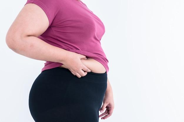 Толстые женщины используя две руки, чтобы удержать лишний жир в области ее талии