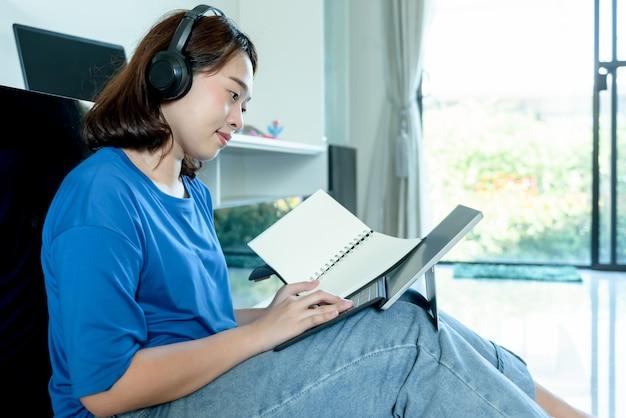 Азиатский женский студент университета носить наушники и смотреть ноутбук
