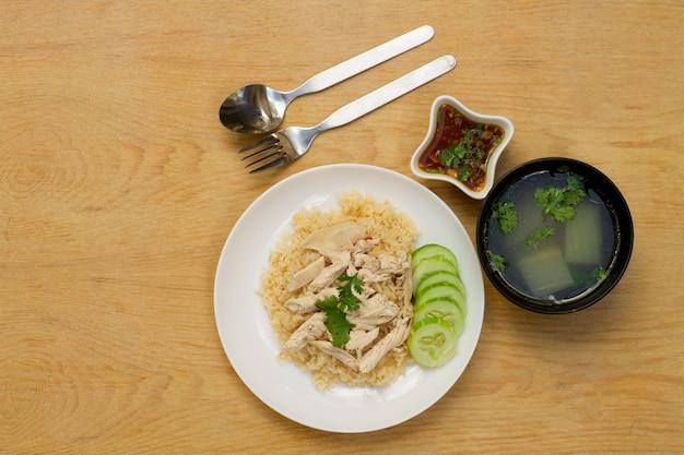 テキストのためのスペースと木製のテーブルの白いプレートの米と蒸しチキン。