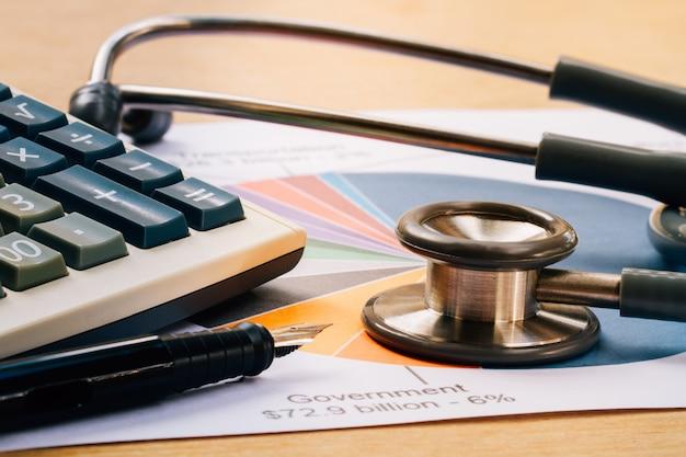 医療用ヘッドホン、机の上に財務報告書の図表と電卓を備えた聴診器