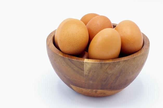白い背景の上の木製のボウルに新鮮な鶏の卵