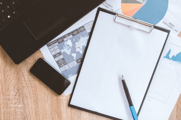書類、コンピューター、タッチスクリーンデバイス、文房具、木製の表面、トップビューで実業家の整頓されたデスクトップと作業ツール
