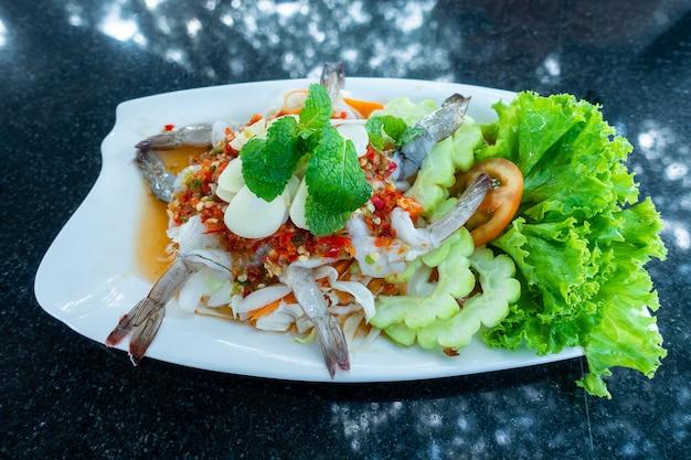 野菜と緑のスパイシーソースタイ料理の白い皿に魚醤で冷やしたエビ