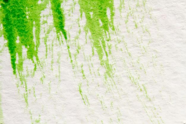 抽象的な手描きの白い紙の上の緑の水彩スプラッシュ