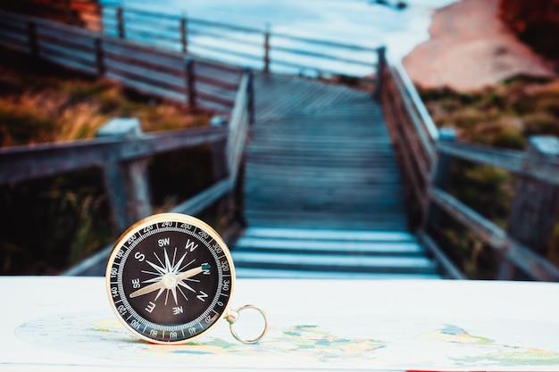 Закройте вверх по компасу на бумажной карте, путешествии и образе жизни, управляйте к концепции технологии дела успеха.
