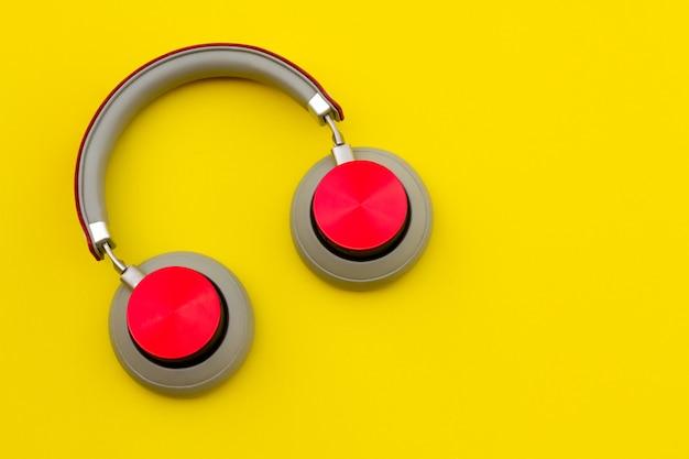 Красные наушники на желтом фоне. музыкальная концепция.