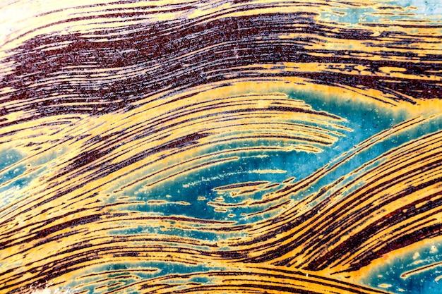 古い汚れたひび割れた風化壁の塗料が錆びた金属板を剥がしています。テクスチャ背景
