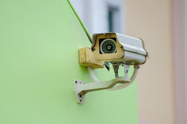 Серебряная камера видеонаблюдения на зеленой стене закрытая телевизионная камера на зеленом фоне