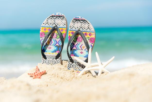 Закройте вверх по сандалиям на песчаном пляже с песчаным пляжем морских звёзд. концепция лета и отдыха