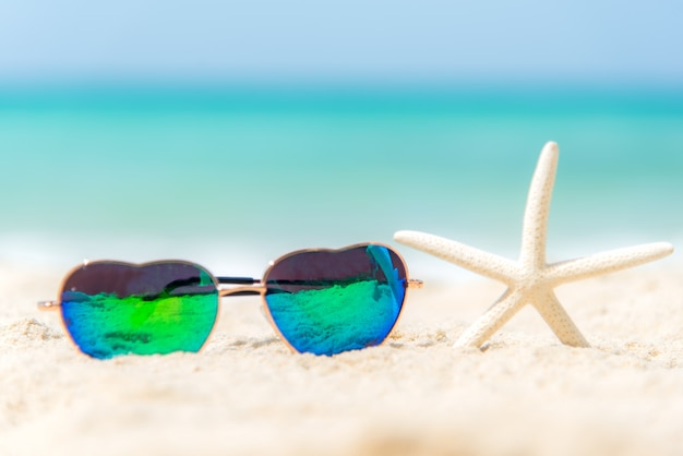 Солнечные очки формы жары моды лета на пляже моря под ясным голубым небом. летний отдых расслабиться фон, копировать пространство.