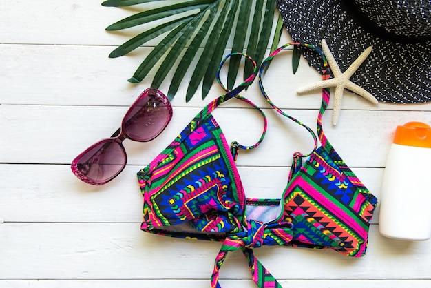 夏のファッションの女性の水着ビキニ、カメラ、ヒトデ、日焼け止め、サングラス、帽子。ホリデーウッドホワイトバックグラウンドで旅行します。夏のコンセプト。
