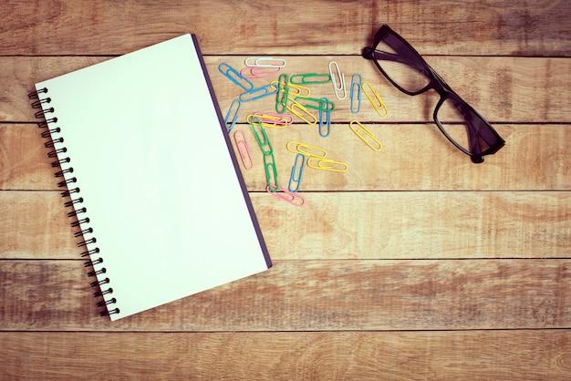 Блокнот и очки на деревянный стол для работы