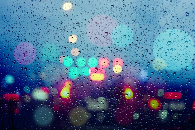 雨の中で軽い車からボケ味を持つ抽象的な背景をぼかした写真