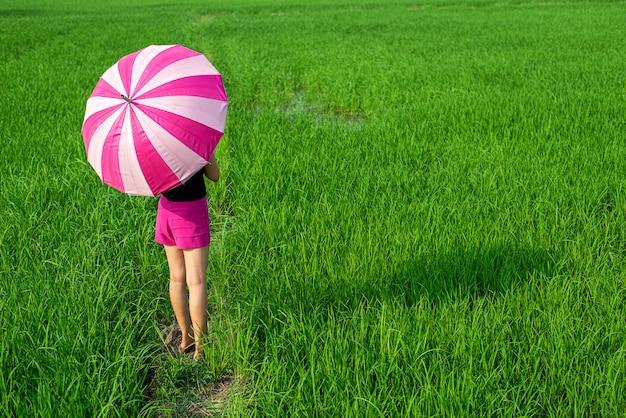 Женщина, стоящая в зонтике на зеленом лугу